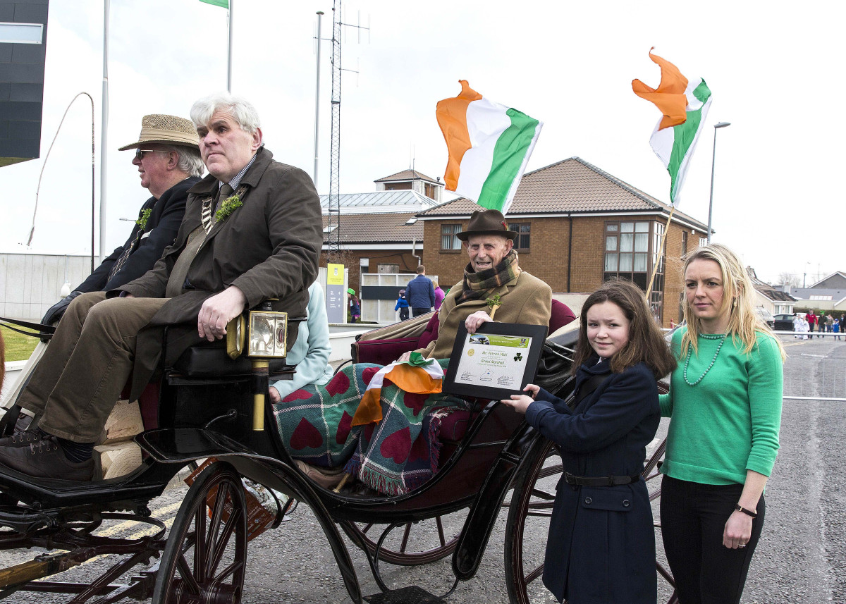 "Ennis St Patrick's Day Parade Grand Marshall Patrick Pakie Wall pictured at the beginning of the 2016 Parade receiving a ""Certificate of Recognition"" from by Anna Whelan, 5th class pupil and her teacher Helen McMahon, Ballyea N.S. where Pakie attended from 1923 to 1931."