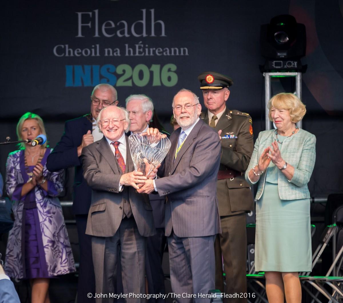 President Michael D. Higgins makes a presentation to Micheál Ó Riabhaigh.